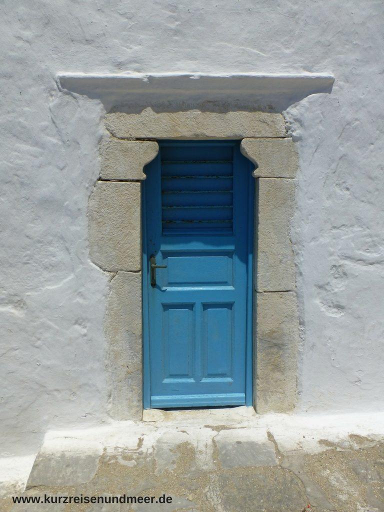 Das Bild zeigt eine blaue Tür in einer weißen Mauer.