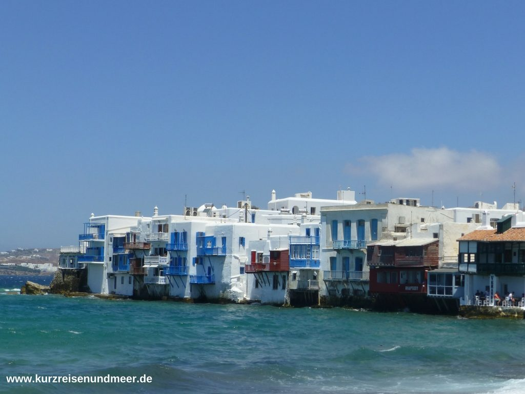 Das Bild zeigt Häuser in Mykonos Stadt direkt am Wasser
