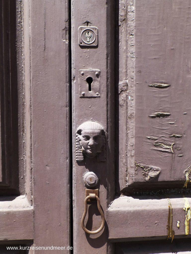 Das Bild zeigt eine alte Tür und über dem Schlüsselloch befindet sich zur Verzierung ein Kopf mit einem typischen ägyptischen Kopftuch. (Beitrag zur Foto-Blogparade)