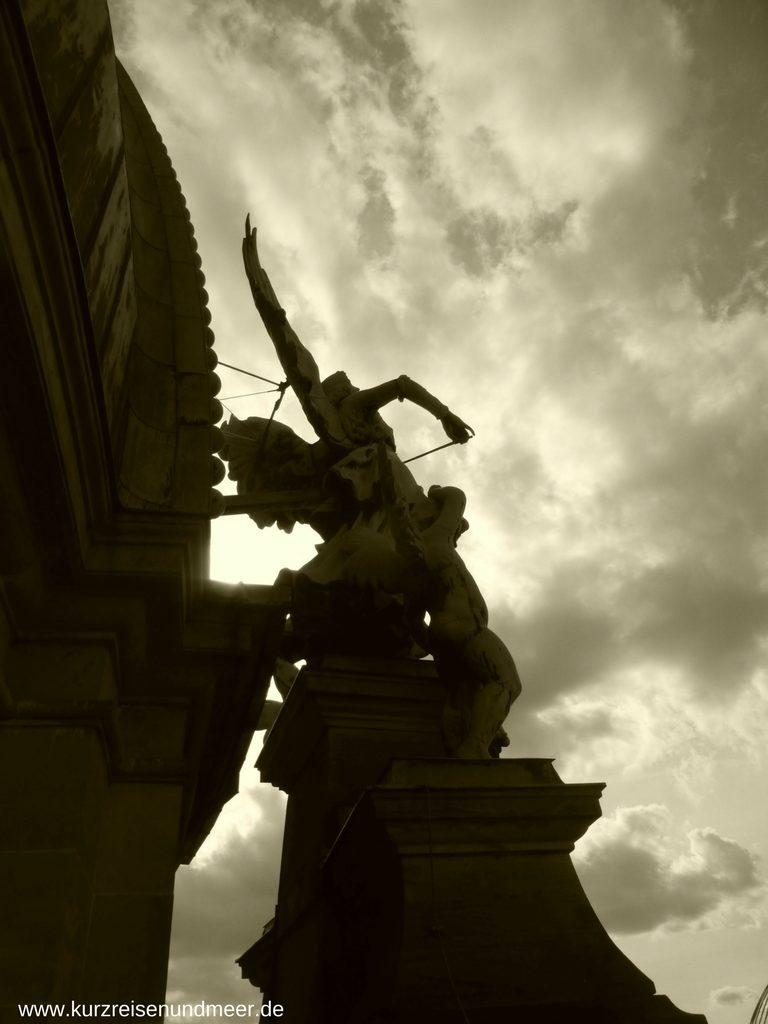Ein dramatisches Bild: Ein geigespielender Engel vor dem Wolkenhimmel
